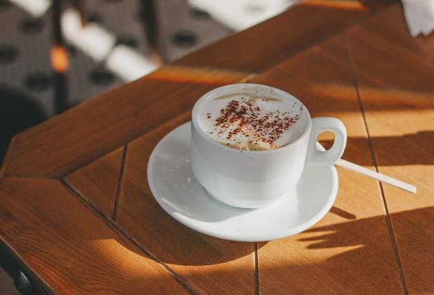 Tasse de café cappuccino avec mousse et cannelle sur une table en bois. Photo Premium