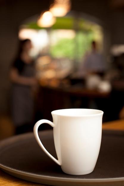 Tasse à café en céramique blanche sur un plateau au café Photo gratuit