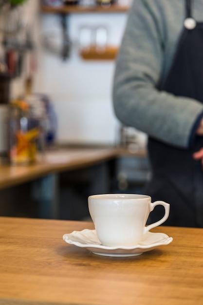 Tasse à café en céramique et soucoupe sur le comptoir du café Photo gratuit
