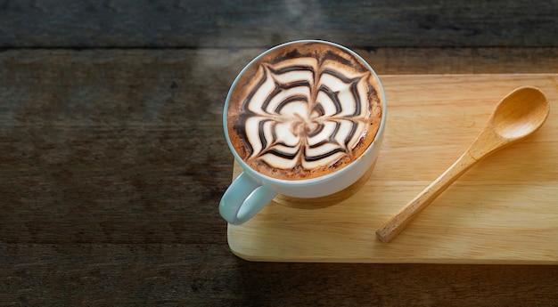 Tasse de café chaud avec une belle décoration d'art latte sur une table en bois ancienne texture Photo gratuit