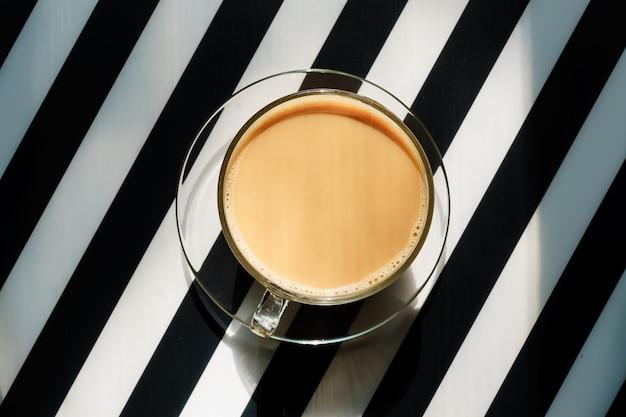 Tasse De Café Chaud Avec Du Lait Sur Un Fond Rayé Noir Et Blanc. Espace Copie Photo Premium
