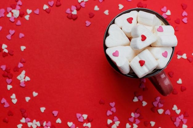 Tasse de café chaud avec des guimauves en forme de coeur et confetties sur le rouge Photo gratuit