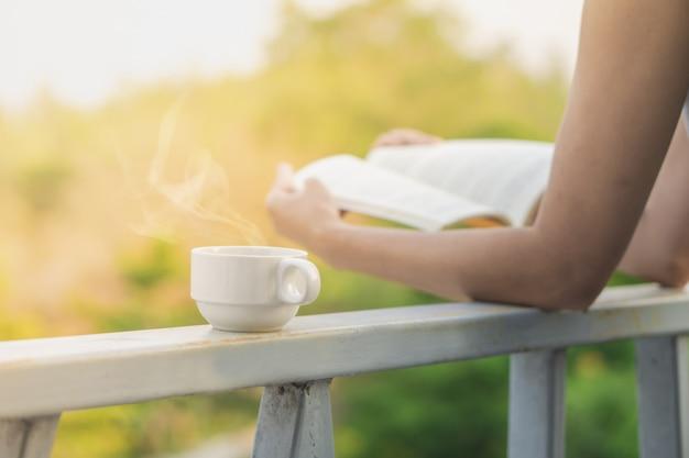 Tasse de café chaud avec un livre de lecture de femme en plein air Photo Premium