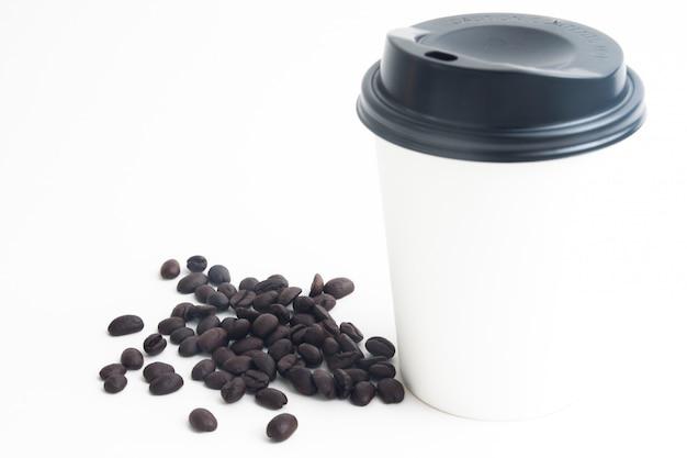 Une tasse de café chaud mock up pour marque ou logo avec des grains de café torréfiés sur fond blanc Photo Premium