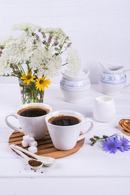 Tasse De Café Chicorée Thé Boisson Boisson Chaude Avec Fleur De Chicorée Et Biscuits Au Sucre Sur Un Tableau Blanc. Nature Morte Avec Petit Déjeuner Photo Premium