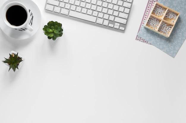 Tasse à café; clavier; usine de cactus et boîte avec des papiers de carte sur le lieu de travail Photo gratuit