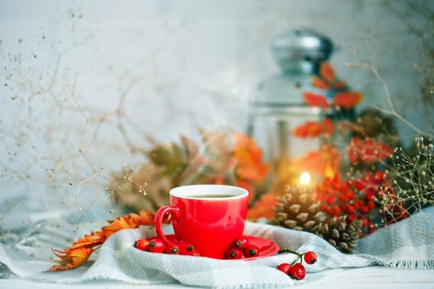 Tasse de café, des cônes et des feuilles d'automne sur une table en bois. Photo Premium