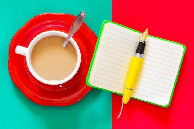 Une Tasse De Café à Côté D'un Cahier Vert Et D'un Stylo-plume Jaune, Tout Est Prêt Pour Prendre Des Notes Ou Organiser La Journée Dès Le Petit-déjeuner. Photo Premium