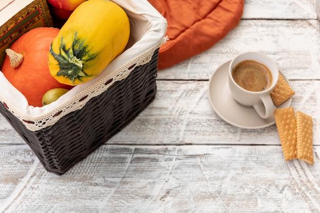 Tasse de café à côté du panier avec des citrouilles Photo gratuit