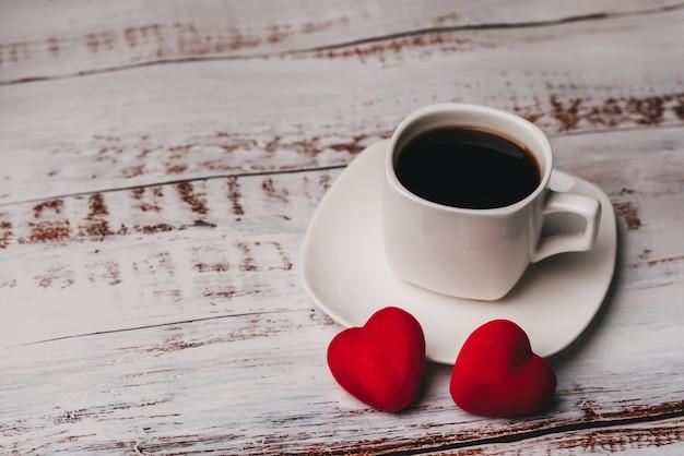 Tasse de café et un couple de coeurs rouges de saint valentin sur une table en bois blanche. le concept de carte de voeux Photo Premium