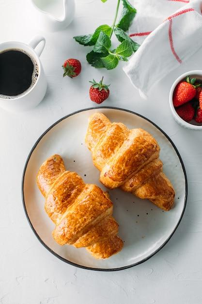 Tasse de café, croissants fraîchement cuits au four et fraises fraîches sur fond en bois Photo Premium