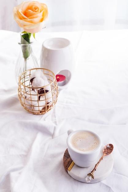 Tasse de café du matin avec des lunettes sur un cahier, une bougie et une rose sur un lit blanc Photo Premium