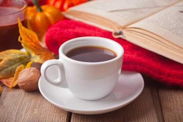 Tasse de café, feuilles d'automne, bougie, citrouille, livre et couverture. Photo Premium