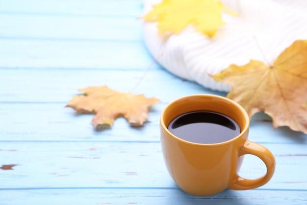 Tasse de café avec des feuilles d'automne et pull sur fond en bois Photo Premium