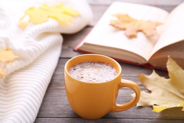Tasse de café avec des feuilles d'automne et vieux livre sur fond en bois Photo Premium