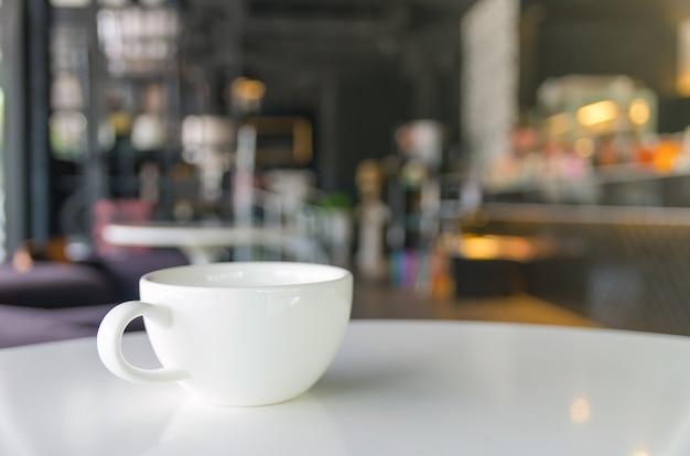 Tasse de café sur fond de café flou Photo Premium