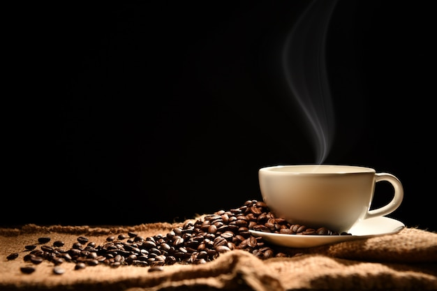 Tasse de café avec de la fumée et des grains de café sur fond en bois Photo Premium