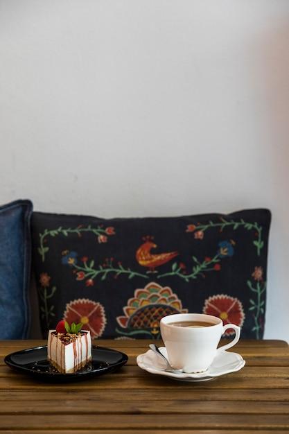 Tasse à café et gâteau au fromage sur une table en bois devant le coussin contre le mur blanc Photo gratuit