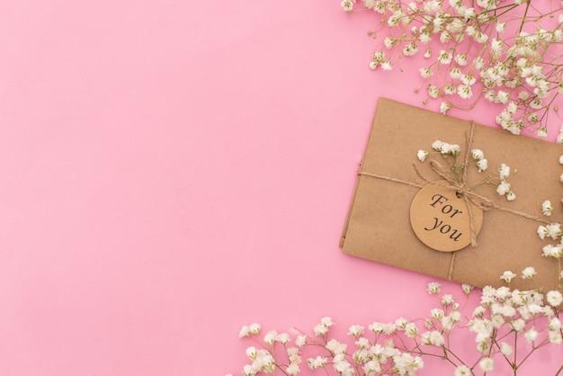 Tasse de café, gâteau macaron, boîte de cadeau ou cadeau et fleur sur la table lumineuse d'en haut le matin. Photo Premium