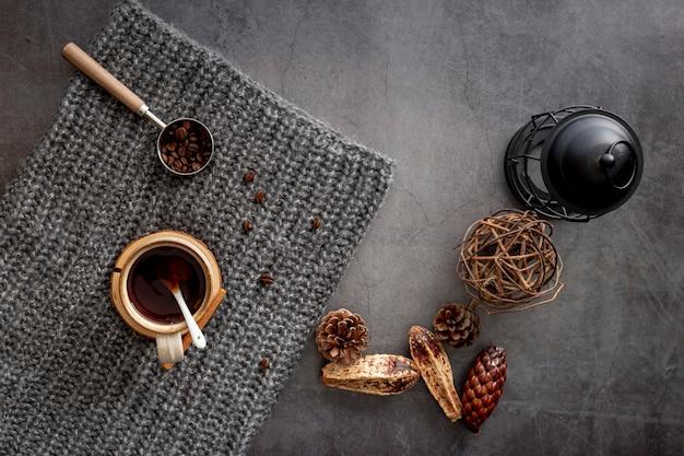 Tasse à café avec des grains de café sur une écharpe grise Photo gratuit
