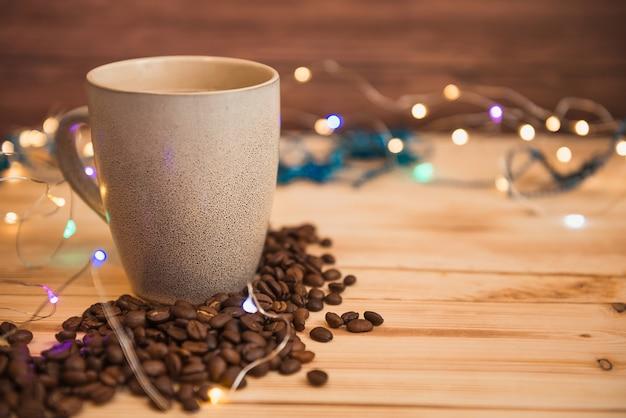 Tasse à café et grains de café épars, lumières de noël sur fond, mise au point sélective. Photo Premium
