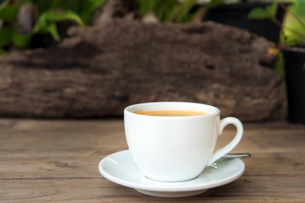 Tasse de café avec des grains de café sur la table en bois Photo Premium