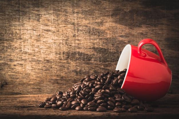 Tasse à café et haricots sur fond de bois Photo Premium
