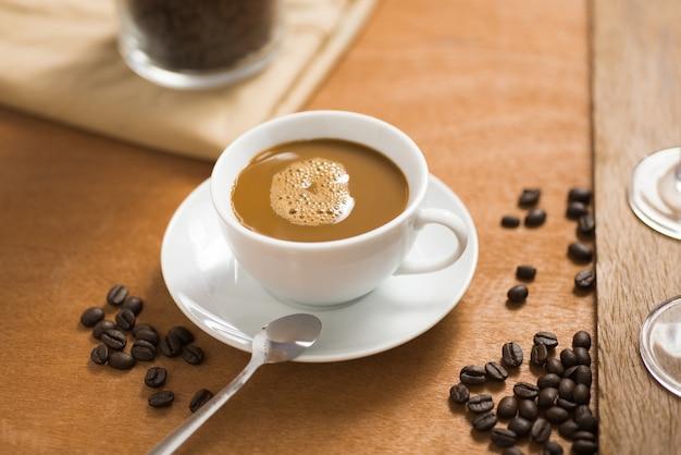 Tasse à café avec des haricots sur une table en bois dans un café Photo Premium