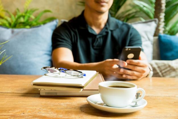 Tasse de café avec l'homme à l'aide d'un téléphone portable et livre sur la table. Photo Premium