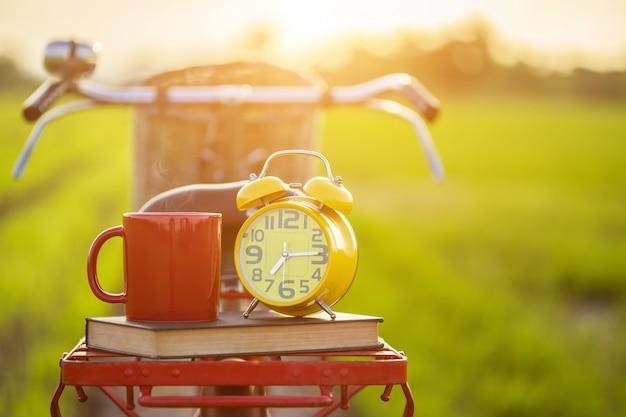 Tasse à café, horloge et livre posés sur le vélo classique de style japon rouge devant un champ de riz vert Photo Premium