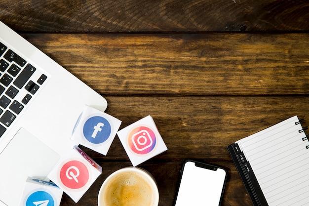 Tasse de café avec des icônes d'application près de mobile et ordinateur portable Photo gratuit