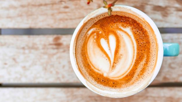 Tasse à café avec latte forme de coeur sur la table en bois Photo gratuit