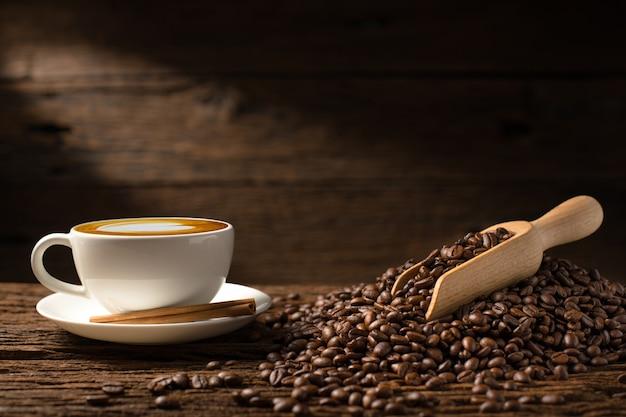 Tasse De Café Latte Et Grains De Café Sur Le Vieux Fond En Bois Photo Premium