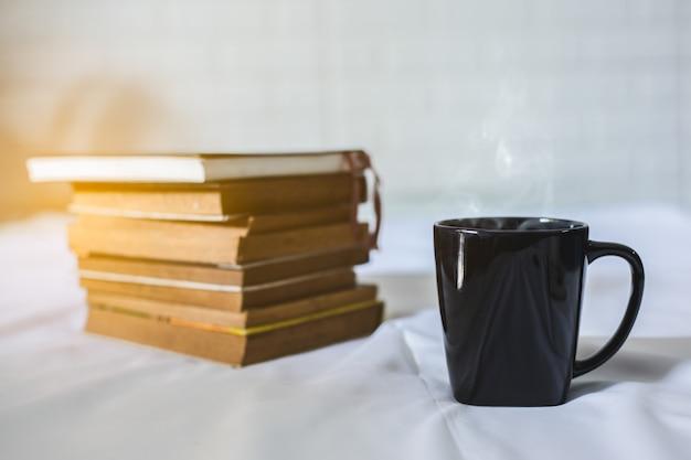 Tasse de café et un livre sur un lit. tasse blanche avec du café sur un livre. fermer Photo Premium