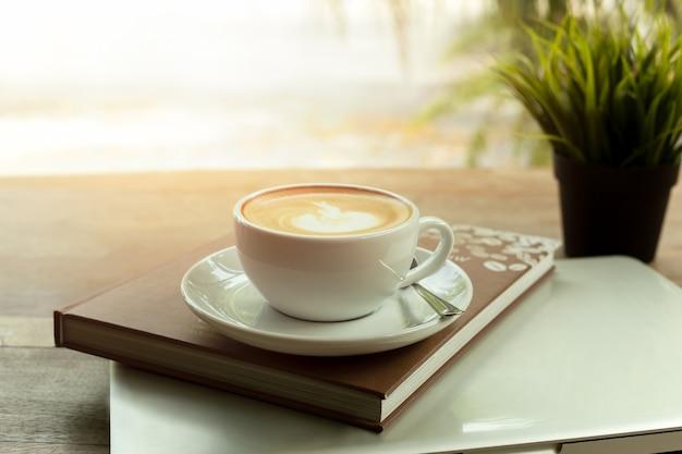 Tasse de café sur le livre et l'ordinateur portable sur une table en bois le matin. Photo Premium