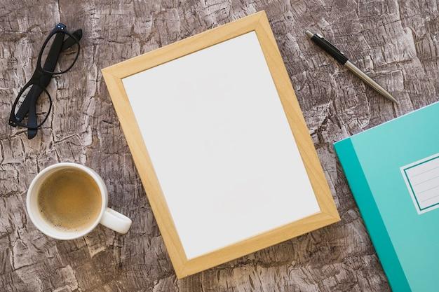 Tasse à café; lunettes; cadre; stylo et cahier sur fond texturé Photo gratuit