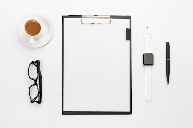 Tasse à café, lunettes, montre intelligente, stylo et presse-papiers blanc sur le bureau blanc Photo gratuit