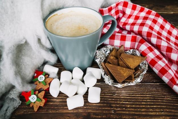 Tasse à café; morceaux de chocolat et guimauve sur un bureau en bois à noël Photo gratuit