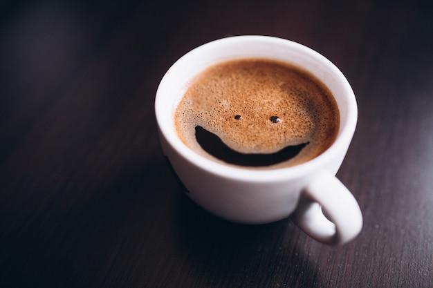Tasse de café avec de la mousse, sourire visage, sur bureau isolé Photo gratuit