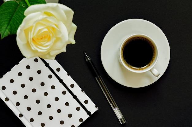 Tasse De Café Noir, Carnet Et Rose Blanche Sur Fond Noir Photo Premium