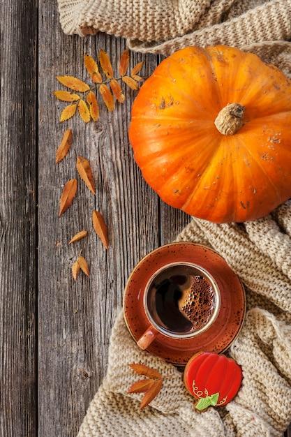 Tasse de café noir chaud et pain d'épice en forme de citrouille avec des feuilles automnales, citrouille et écharpe chaude. Photo Premium