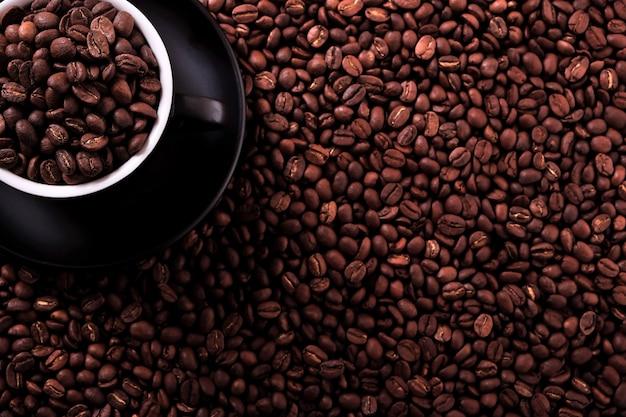 Tasse à café noire avec fond de haricots grillés Photo gratuit