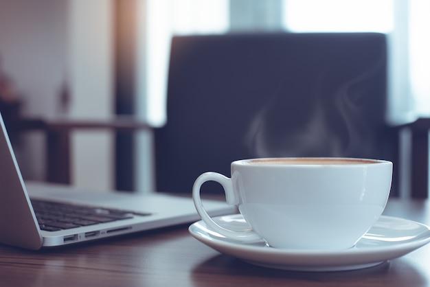 Tasse de café et ordinateur portable sur une table en bois avec siège vide Photo Premium