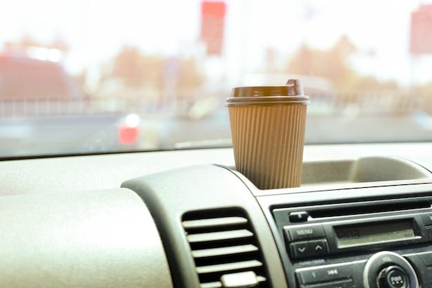 Une tasse de café en papier sur le tableau de bord dans la voiture. Photo Premium