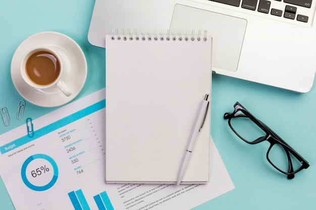 Tasse de café, plan budgétaire, bloc-notes à spirale, stylo, lunettes et ordinateur portable sur fond bleu Photo gratuit