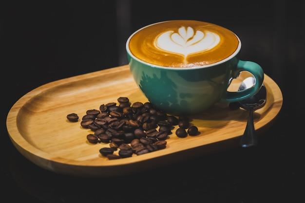 Une tasse de café sur une plaque de bois Photo Premium