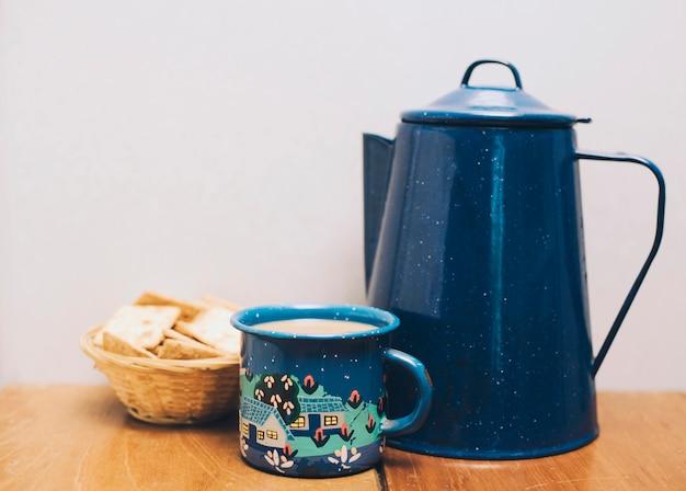 Tasse à café en porcelaine bleu foncé avec craquelins sur le bureau contre le mur Photo gratuit
