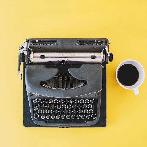 Tasse de café près de la machine à écrire Photo gratuit