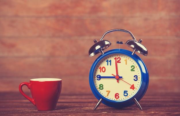 Tasse de café et réveil sur une table en bois. Photo Premium