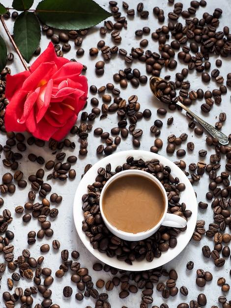 Tasse à café rose rouge en fleurs, grains de café sur le fond sous le béton. Photo Premium